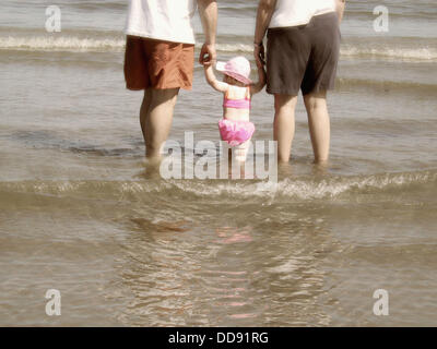 Parents and baby into the water - Stock Photo