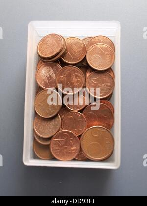Coins of euro cent in a plastic box on a gray background - Stock Photo