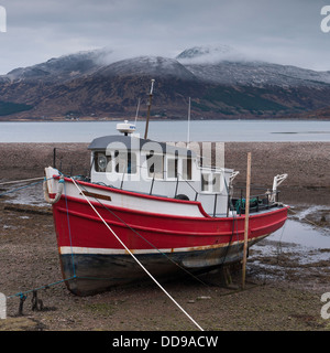 A red fishing boat in Glenelg bay on the west coast of Scotland with the village of Kylerhea across the water, Scotland - Stock Photo
