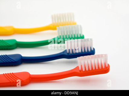 Detail of a row of different colored toothbrushes with the front one in selective focus good for dentists - Stock Photo
