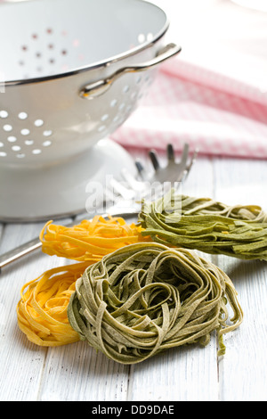 Italian pasta tagliatelle on wooden table - Stock Photo