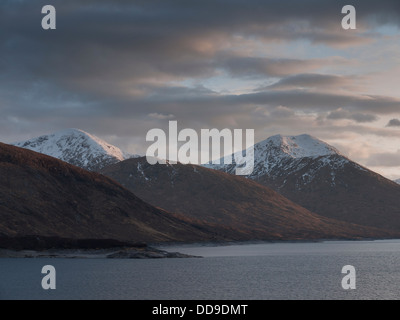 The view across Loch Quoich towards the mountains Sgurr Mor and Sgurr na Fhuarain at sunset, North West Highlands, - Stock Photo