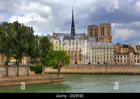 Notre Dame de Paris cathedral among typical parisian buildings along Seine river in Paris, France. - Stock Photo