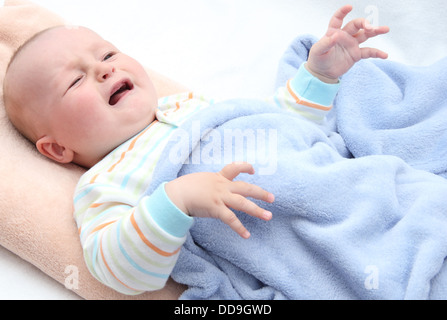 little baby crying in bed - Stock Photo