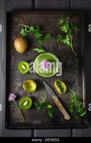 Glass of smoothie with kiwi, parsley and blooming chives, close up - Stock Photo