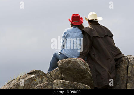 Female and male in western attire sitting together on the rocks out in the country looking off into the distance - Stock Photo