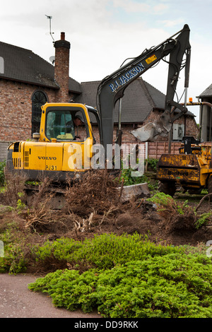 self building house, excavator digging up garden to prepare site for building - Stock Photo