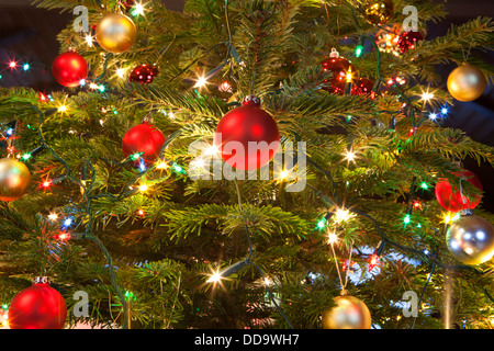 Christmas baubles hanging on tree, close up - Stock Photo