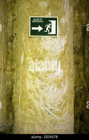 Señal de salida de emergencia en un muro destruido. - Stock Photo