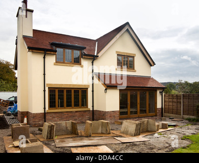 self building house, hard landscaping, sandstone paving slabs around edge of new-built property - Stock Photo