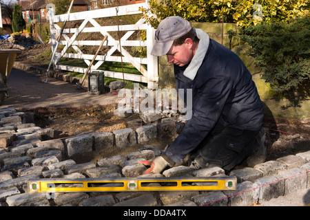 self building house, hard landscaping, craftsman laying reclaimed granite setts at entrance to driveway - Stock Photo