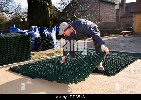 self building house, hard landscaping, craftsman laying plastic sheets of parking mats to be sown with grass - Stock Photo