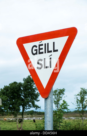 The international road sign for Give Way, with the words in Irish / Gaelic, seen in the West of Ireland - Stock Photo