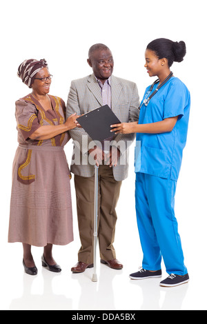 young female African nurse talking to senior couple isolated on white background - Stock Photo