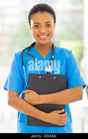 beautiful female African medical nurse holding clipboard - Stock Photo