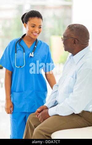 beautiful African medical doctor talking to senior man - Stock Photo