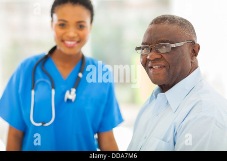 smiling senior African American man in doctors office with nurse on background - Stock Photo