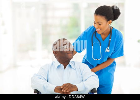 beautiful African nurse taking care of senior patient in wheelchair - Stock Photo