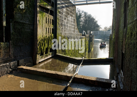 View from drained lock chamber through open gates to canal boat - Five Rise Locks closed for renovation, Leeds Liverpool - Stock Photo
