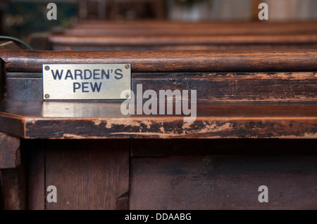 Close-up of metal plaque attached to back of wooden church pew, reading 'Warden's Pew,' a reserved seat for volunteer - Stock Photo
