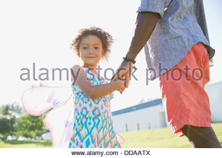 Portrait of cute girl holding fathers hand - Stock Photo
