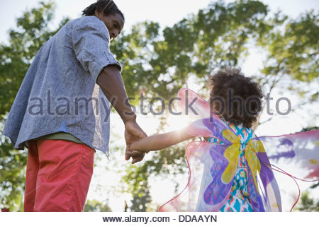 Father and daughter holding hands at park - Stock Photo