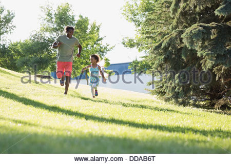 Cheerful father and daughter running in park - Stock Photo