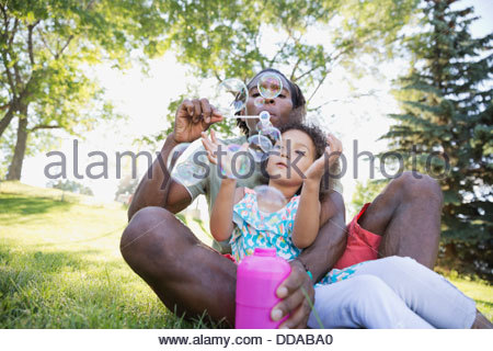 Father and daughter blowing soap-bubbles in park - Stock Photo
