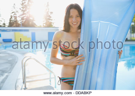 Portrait of teenage girl at swimming pool holding inflatable mat - Stock Photo