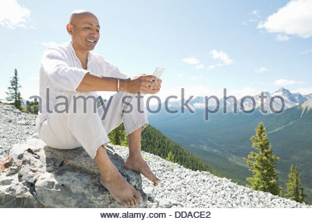 Smiling man using smart phone on mountain top - Stock Photo