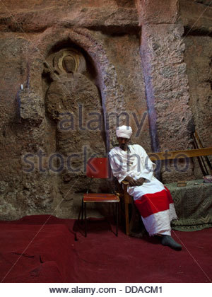 Priest inside the church of The Tomb of Christ, Lalibela - Stock Photo