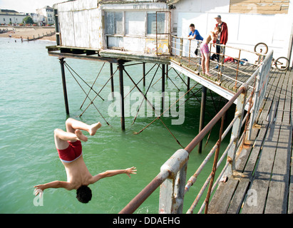A teenage boy dives, or tombstones, off the pier at Bognor Regis. He did a 'back flip' and landed well in the water. - Stock Photo