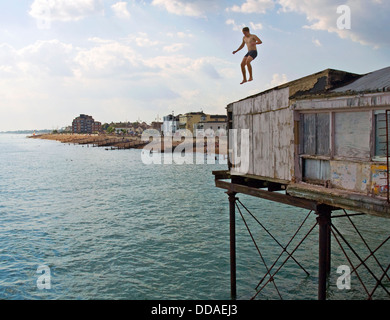 A teenage boy jumps, or tombstones, off a building on the pier at Bognor Regis. He took a running jump and landed - Stock Photo