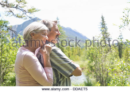 Mature couple enjoying view in forest - Stock Photo