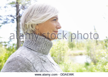 Profile shot of mature woman in forest - Stock Photo