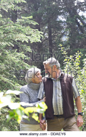 Affectionate couple holding hands while walking through forest - Stock Photo
