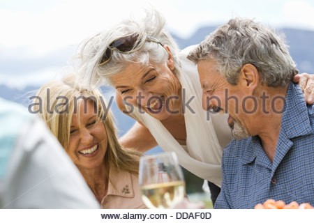 Mature friends having fun at an outdoor picnic - Stock Photo