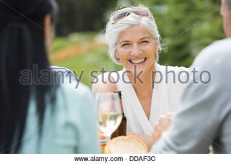 Mature woman smiling outdoors among friends - Stock Photo