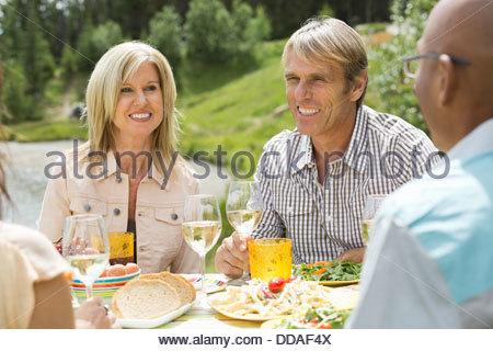 Mature friends enjoying an outdoor picnic - Stock Photo
