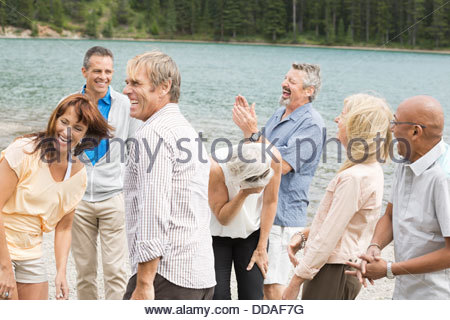 Group of friends laughing on the beach - Stock Photo