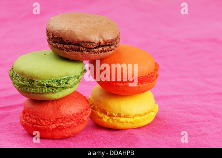 Pile of delicious colorful macaroons on bright pink - Stock Photo