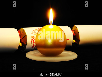 Round gold Christmas candle with a white Christmas cracker set against a black background. - Stock Photo