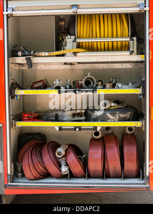 Fire hoses and nozzles inside a fire engine  Derbyshire England - Stock Photo