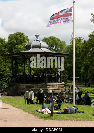 People sitting in front of the Bandstand listening to brass bands  in the Pavilion Gardens Buxton Derbyshire Peak - Stock Photo