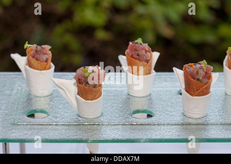 exotic type of design fingerfood based on roasted bread leaf and meat slice with sauce spices served in small white - Stock Photo