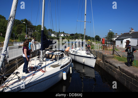 Yacht being guided by the lock keeper into the lock 4 at the Ardrishaig swing bridge on the Crinan Canal in Argyllshire - Stock Photo