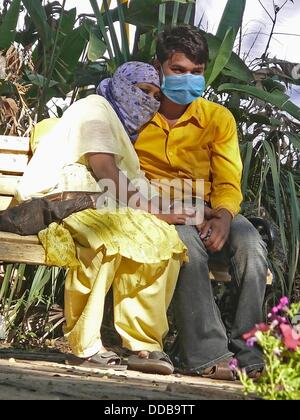 Young couple in a garden with Precaution mask for Swine Flu, H1N1 - Stock Photo