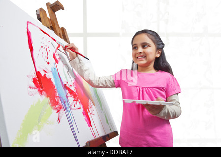 Cute little girl painting on canvas during art class - Stock Photo