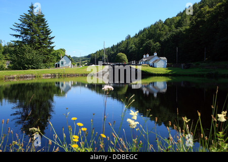 Lock keepers cottages reflected in a still Crinan Canal at Dunardry Bridge in Argyll, Scotland - Stock Photo