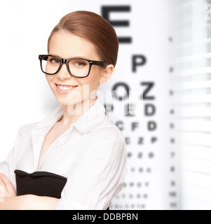 woman in eyeglasses with eye chart - Stock Photo